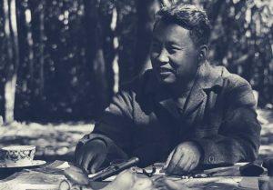 """Saloth Sar, mais conhecido como Pol Pot, nasceu em 1925 em uma família de fazendeiros no Camboja (na época Indochina francesa). O jovem estudou nas melhores escolas e, com 20 anos, viajou a Paris para estudar rádio graças a uma bolsa. Na França, Pol Pot conheceu as ideias marxistas e aproximou-se do Partido Comunista Francês. Retornou ao Camboja em 1953, com 28 anos, unindo-se imediatamente ao movimento comunista e à luta pela independência, conquistada no ano seguinte. Em 1962, Pol Pot assumiu o controle do Partido Comunista do Camboja tornando-se Secretário-Geral (cargo que ocupou até 1981). Fugindo às perseguições do governo de Sihanouk, refugiou-se na floresta, onde começou a organizar e armar um grupo de resistência baseado nas táticas de guerrilha, o Angkor/Khmer Vermelho. Na estrutura do grupo, ele era o """"Irmão número 1"""". Na foto, da década de 1980, Pol Pot no seu santuário de Phnom Malai, na faixa de fronteira com a Tailândia."""