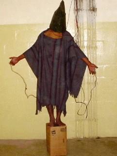 Foto que correu o mundo, de autoria desconhecida, provavelmente captada por carcereiros ou soldados americanos, de tortura na prisão de Abu Ghraib, no Iraque ocupado, em 2003 ou 2004.